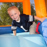 kids party boy-playing-inflatable-slide-26818416